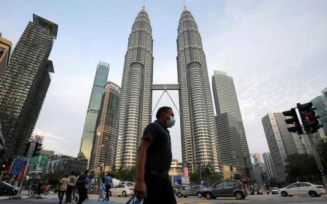 A man wearing a protective mask crosses a street in front of Petronas Twin Towers, amid the coronavirus disease (COVID-19) outbreak in Kuala Lumpur, Malaysia Aug 11, 2020. REUTERS