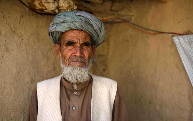 Arsam, 70, who says his house has been destroyed by floods poses for a photo in Share-Buzurg, Afghanistan, June 1, 2020. Thomson Reuters Foundation/Stefanie Glinski