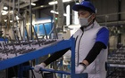 An employee of Marelli?fs factory wearing a protective face mask and a vest equipped with battery-powered fans at the waist, to prevent heatstroke during summer season, is seen amid the coronavirus disease (COVID-19) outbreak, in Ora Town, Gunma Prefecture, Japan Jul 30, 2020. REUTERS