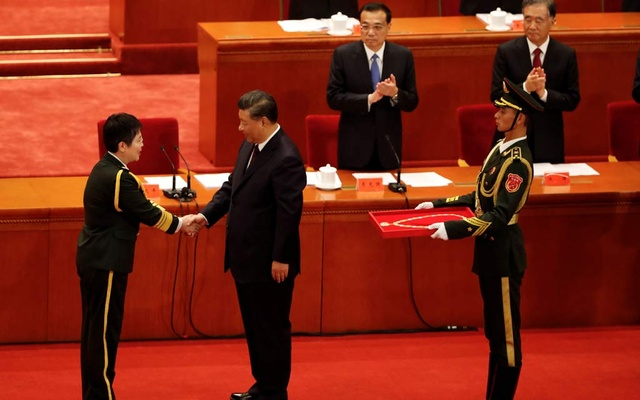 Chinese President Xi Jinping shakes hands with vaccine researcher and People's Liberation Army (PLA) major general Chen Wei during a meeting to commend role models in China's fight against the coronavirus disease (COVID-19) outbreak, at the Great Hall of the People in Beijing, China September 8, 2020. Reuters