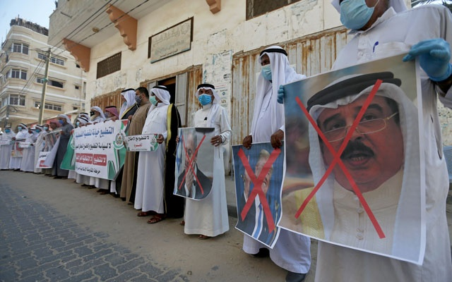 Palestinians hold crossed out posters depicting Bahrain's King Hamad bin Isa Al Khalifa, US President Donald Trump and Israeli Prime Minister Benjamin Netanyahu during a protest against Bahrain's move to normalise relations with Israel, in the central Gaza Strip September 12, 2020. REUTERS