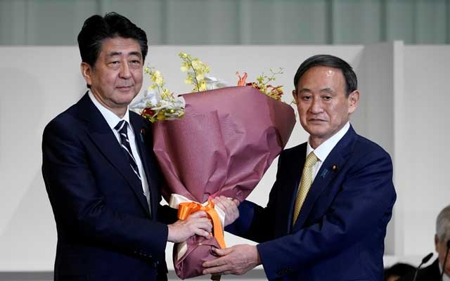 Japan's Prime Minister Shinzo Abe presents Chief Cabinet Secretary Yoshihide Suga with flowers after he was elected as new head of the ruling party at the Liberal Democratic Party's (LDP) leadership election in Tokyo, Japan Sept 14, 2020. REUTERS