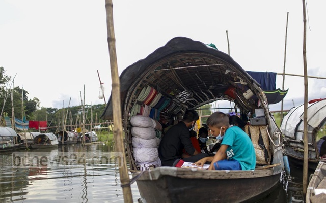 Two young teachers from Alokito Shishu school are seen conducting classes on a boat. Since the school is closed, the teachers themselves visit the students in their boats and conduct classes there.
