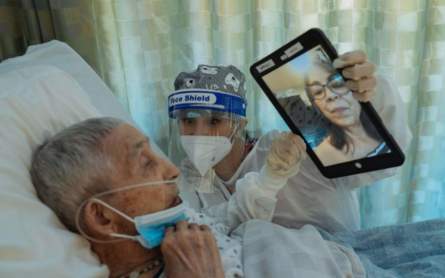Maika Alvarez helps Jose Montoya speak with his daughter via FaceTime at the Canyon Transitional Rehabilitation Center in Albuquerque, NM, August 2020. Every resident at the long-term care facility has COVID-19 and relies on care providers for medical care and moments of connection. (Isadora Kosofsky/The New York Times)