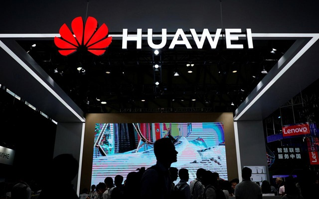 FILE PHOTO: People walk past a sign board of Huawei at CES (Consumer Electronics Show) Asia 2018 in Shanghai, China June 14, 2018. REUTERS/Aly Song/File Photo