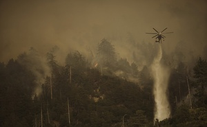A helicopter drops water as firefighters battle the El Dorado Fire in Angelus Oaks, Calif., Tuesday, Sept. 15, 2020. (Eric Thayer/The New York Times)