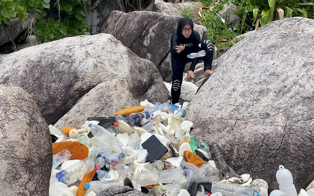A woman clears trash by the sea at Tioman Island, Pahang, Malaysia, Sept 13, 2020, in this still image from video obtained via social media. REUTERS