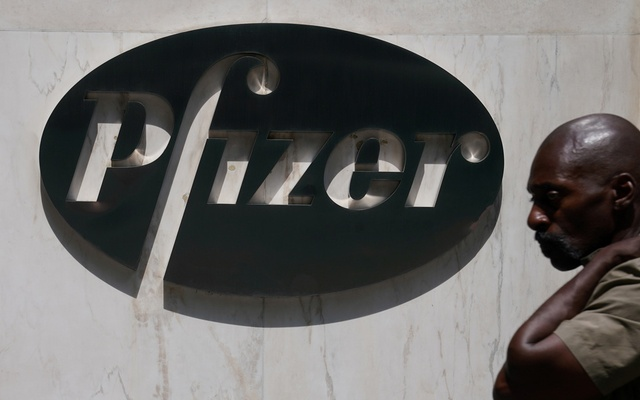 A man walks past a sign outside Pfizer Headquarters in the Manhattan borough of New York City, New York, US, July 22, 2020. REUTERS