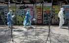 FILE PHOTO: Medical workers wearing protective suits pass by barbed wire in a red zone under enhanced lockdown, amid the novel coronavirus outbreak, in Petaling Jaya, Malaysia, May 11, 2020. REUTERS/Lim Huey Teng/File Photo