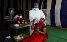 A health worker wearing personal protective equipment (PPE) collects a swab sample from a woman, amidst the spread of the coronavirus disease (COVID-19), at a vegetable market, in New Delhi, India, September 18, 2020. REUTERS