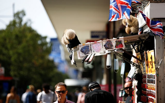 A man walks underneath a selection of protective face masks for sale on Oxford Street, amid the coronavirus disease (COVID-19) outbreak, in London, Britain, September 17, 2020. Reuters