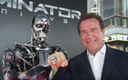 Arnold Schwarzenegger poses by a Terminator replica at the premiere of