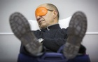 A man attempts to sleep on his suitcase at John F. Kennedy International Airport in New York January 22, 2014. REUTERS