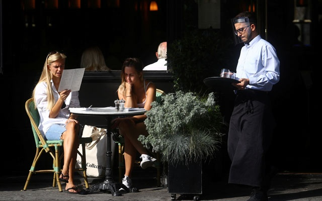 A waiter wears a face shield as women are seen in an outdoor seating at a restaurant, amid the spread of the coronavirus disease (COVID-19) in Chelsea, London, Britain September 22, 2020. Reuters