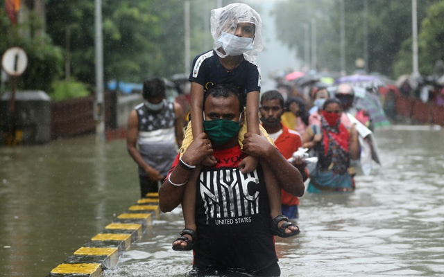 A man carries a child through a waterlogged road after heavy rainfall in Mumbai, India, Sept 23, 2020. REUTERS