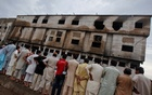 Residents stand outside a garment factory that caught fire the day before, in Karachi September 13, 2012. Reuters