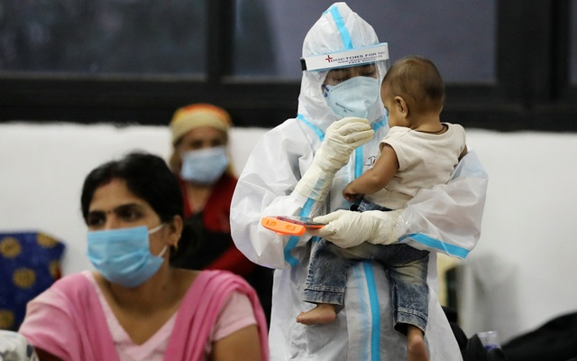 A medical worker in personal protective equipment (PPE) plays with a child of woman recovering inside a quarantine centre for the coronavirus disease (COVID-19) patients amidst the spread of the disease at an indoor sports complex in New Delhi, India, September 22, 2020. REUTERS