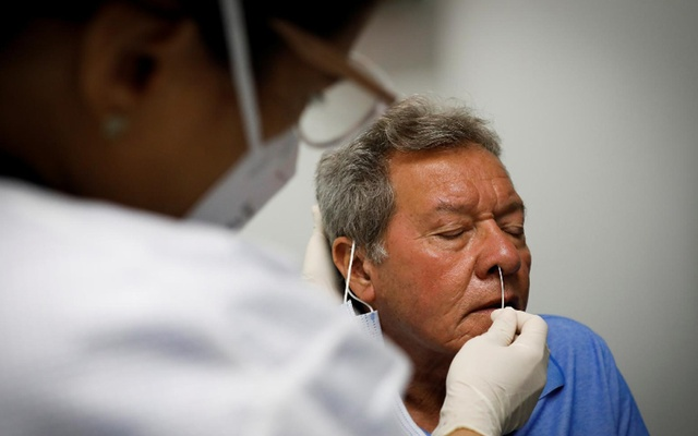 A volunteer reacts while a swab sample is taken as he participates in a coronavirus disease (COVID-19) vaccination study at the Research Centers of America, in Hollywood, Florida, US, Sept 24, 2020. REUTERS