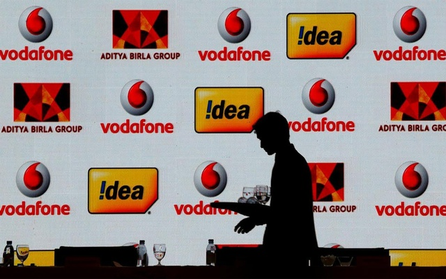 A hotel employee clears a table after Vodafone Group and Idea Cellular news conference in Mumbai, India March 20, 2017. Reuters