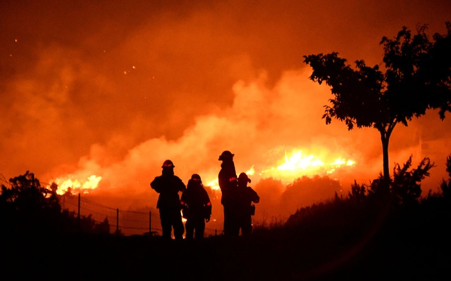 FILE PHOTO: Los Angeles County firefighters keep watch on the Bobcat Fire as it burns through the night in Juniper Hills, California, US September 19, 2020. REUTERS