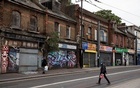 Pedestrians walk past shuttered and bordered up retails stores, amid the spread of the coronavirus disease (COVID-19), in Croydon, south London, Britain, September 27, 2020. REUTERS