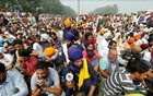 Farmers sit on a road as they block a national highway during a protest against farm bills passed by India's parliament, in Shambhu in the northern state of Punjab, India, September 25, 2020. REUTERS