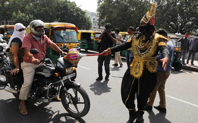 A volunteer of District Magistrate (DM) office dressed as Yamraj, or Hindu God of death, stops people for not wearing masks, amidst the spread of the coronavirus(COVID-19) disease, in New Delhi, India, September 28, 2020. REUTERS