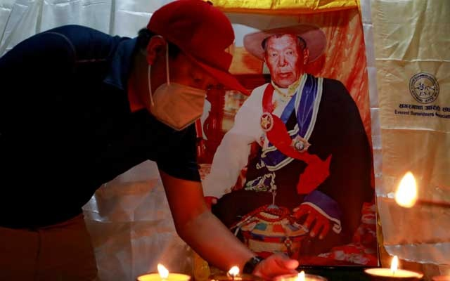 A family member offers a butter lamp near the body of Ang Rita Sherpa, also known as the 'snow leopard' for his climbing skills, who climbed Everest 10 times without the use of supplement oxygen, inside a Sherpa Monastery in Kathmandu, Nepal Sept 22, 2020. REUTERS