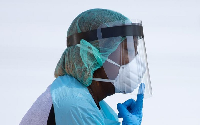 A healthcare worker points to her mask, while requesting a resident to lower their mask to their mouth, at a coronavirus disease (COVID-19) drive in testing location in Houston, Texas, U.S., August 18, 2020. REUTERS/Adrees Latif