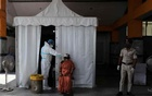 A healthcare worker wearing personal protective equipment (PPE) collects a swab sample from a woman, amid the spread of the coronavirus disease (COVID-19), in New Delhi, India, September 29, 2020. REUTERS