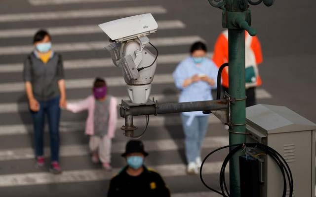FILE PHOTO: A CCTV security surveillance camera overlooks a street as people walk following the spread of the coronavirus disease (COVID-19) in Beijing, China May 11, 2020. REUTERS/Thomas Peter