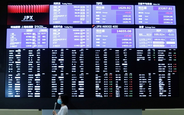 A TV reporter stands in front of a large screen showing stock prices at the Tokyo Stock Exchange after market opens in Tokyo, Japan October 2, 2020. REUTERS