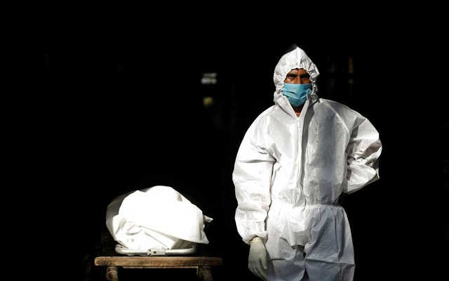 A health worker wearing personal protective equipment (PPE) stands next to a body of a man who died due to the coronavirus disease (COVID-19) before his cremation at a crematorium in New Delhi, India, September 28, 2020. REUTERS