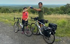 A photo provided by Megan Lui shows the writer Sebastian Modak and his partner, Maggie, celebrating their arrival in the Catskills in upstate New York with cold beers. The hills might not look like much from a car, but on a bike, the Catskills are definitely a climb. (Megan Lui via The New York Times)