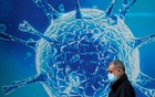 A man wearing a protective face mask walks past an illustration of a virus outside a regional science centre, as the city and surrounding areas face local restrictions in an effort to avoid a local lockdown being forced upon the region, amid the coronavirus disease (COVID-19) outbreak, in Oldham, Britain August 3, 2020. REUTERS