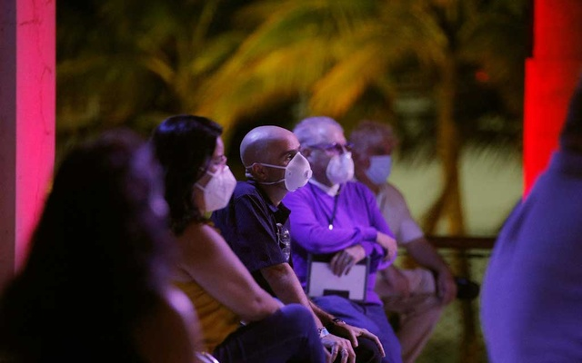 Attendees wearing face masks to protect against the coronavirus disease (COVID-19) watch as US Democratic presidential candidate and former Vice President Joe Biden addresses an NBC News town hall event while campaigning for president in Miami, Florida, US, Oct 5, 2020. REUTERS