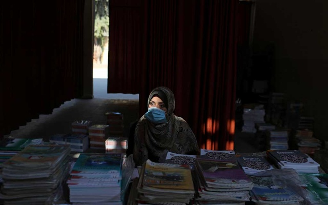 A Palestinian teacher wears a protective face mask as she waits to hand out books to students at a school as part of preparations by the ministry of education to reopen schools amid the coronavirus disease (COVID-19) outbreak, in the northern Gaza Strip Oct 6, 2020. REUTERS