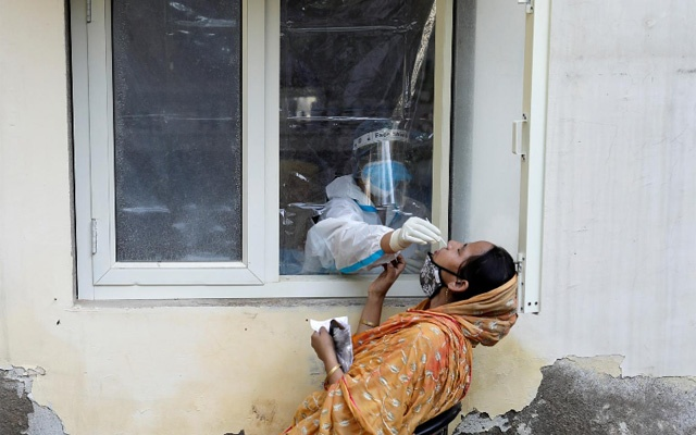 A health worker in personal protective equipment (PPE) collects a sample using a swab from a person at a local health centre to conduct tests for the coronavirus disease (COVID-19), amid the spread of the disease, in New Delhi, India October 7, 2020. REUTERS