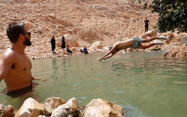 A man jumps into the waters of a natural spring to cool off during a heat wave, amid the coronavirus disease (COVID-19) crisis, near Jericho in the Israeli-occupied West Bank Sept 7, 2020. REUTERS