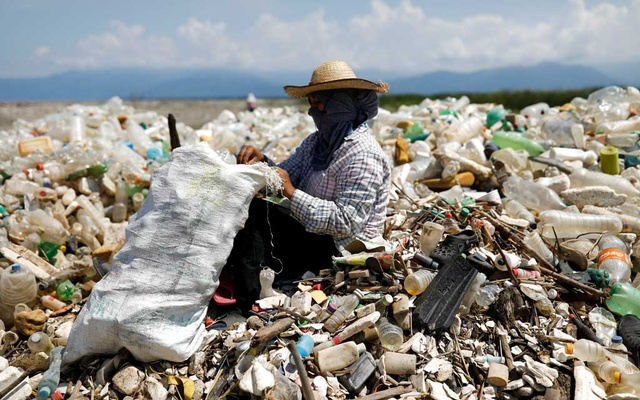 A worker collects plastic bottles in a sack while sitting in a pile of trash washed-up from the Motagua river during a cleaning operation at a beach in the village of Quetzalito, in Puerto Barrios, Guatemala September 24, 2020. Picture taken September 24, 2020. REUTERS