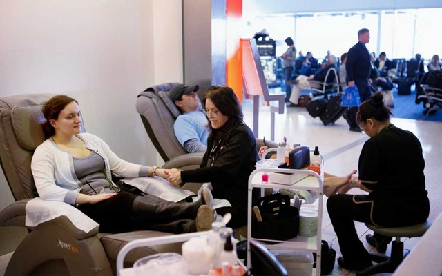 Xpress Spa customers get manicures and massages in John F Kennedy International Airport in New York, March 27, 2014. The New York Times