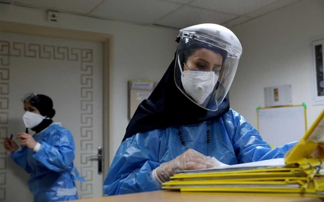 A nurse wearing a protective suit and mask checks the files at Hazrate Ali Asghar Hospital amid the coronavirus disease (COVID-19), in Tehran, Iran September 27, 2020. West Asia News Agency via REUTERS