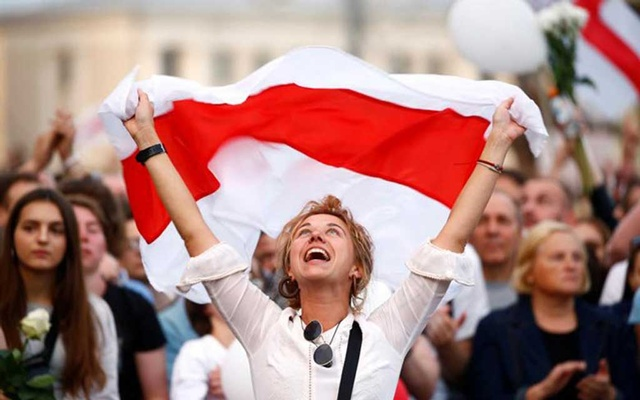 A demonstrator reacts while holding the historical white-red-white flag of Belarus during an opposition demonstration to protest against police violence and to reject the presidential election results near the Government House in Independence Square in Minsk, Belarus August 14, 2020. REUTERS/Vasily Fedosenko