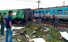 Rescue workers stand at the crash site where a train collided with a passenger bus in Chacheongsao province in central Thailand October 11, 2020. Dailynews via REUTERS