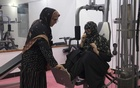 Maryam Durani, left, guides a gym member through an exercise at her fitness club for women in Kandahar, Afghanistan, on Oct 3, 2020. Women agreed to be photographed only while wearing fully concealing clothing instead of their usual workout clothes. (Farzana Wahidy/The New York Times)