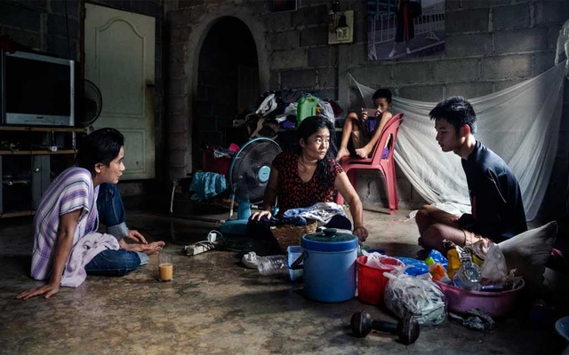 Former child soldier Johnny Htoo, left, at home with his cousins in Ratchaburi, Thailand, on April 5, 2020. He and his twin brother Luther, the leaders of Myanmar's God's Army, were once thought to have magical powers; now adults, they are contending with the trauma of exile, alcohol and loss. (Adam Dean/The New York Times)