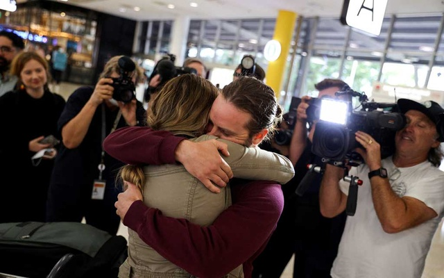 Adam Draper and his partner Stacey Brown embrace each other as she arrives from New Zealand after the Trans-Tasman travel bubble opened overnight, following an extended border closure due to the coronavirus disease (COVID-19) outbreak, at Sydney Airport in Sydney, Australia, October 16, 2020. REUTERS