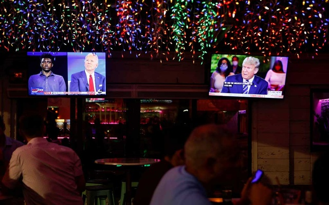 The dual town halls of US Democratic presidential candidate Joe Biden and US President Donald Trump, who are both running in the 2020 US presidential election, are seen on television monitors at Luv Child restaurant ahead of the election in Tampa, Florida, US October 15, 2020. REUTERS