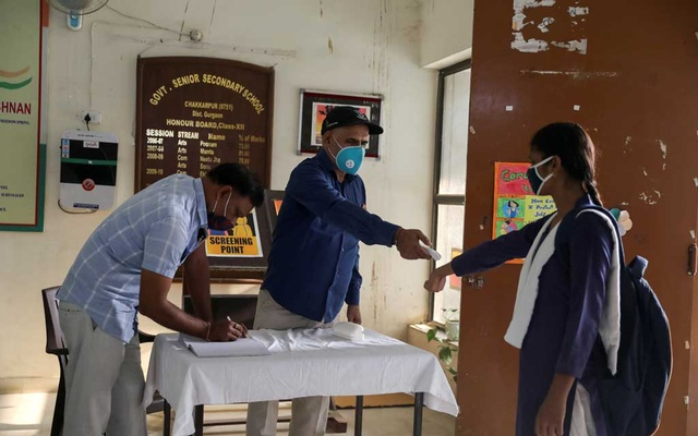 A student wearing a protective face masks gets her temperature checked at a government-run school after authorities ordered schools to reopen voluntarily for classes 9 to 12, amidst the coronavirus disease (COVID-19) outbreak, in Gurugram, India October 15, 2020. REUTERS