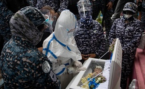 Detained Filipino activist Reina Mae Nasino, in a hazmat suit for protection against the coronavirus, mourns over her three-month-old daughter's coffin, who died while she was in jail, in Manila North Cemetery, Philippines, October 16, 2020. Reuters